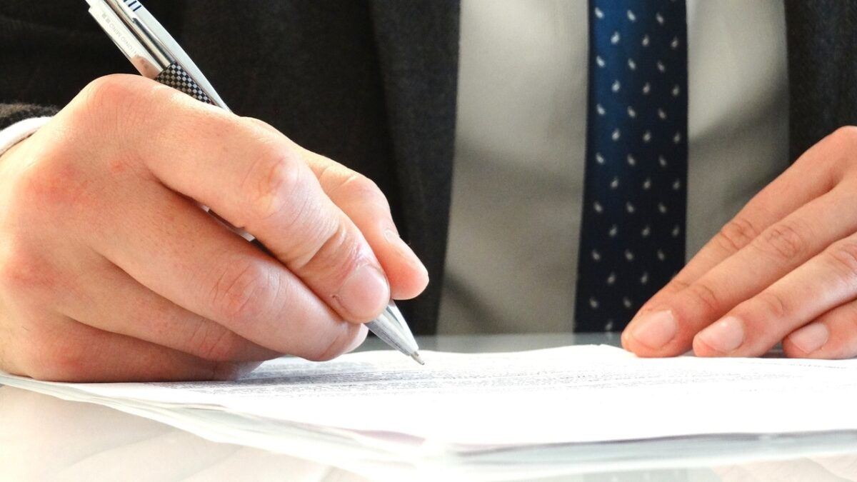 mão assinando documento sobre militar reformado