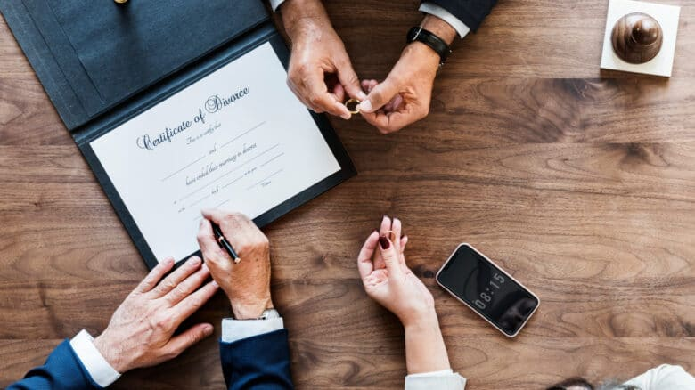 advogados em volta de um documento que oficializa o divórcio extrajudicial